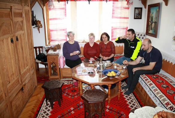 Friends having coffee in a home with hand-carved furniture in Konjic